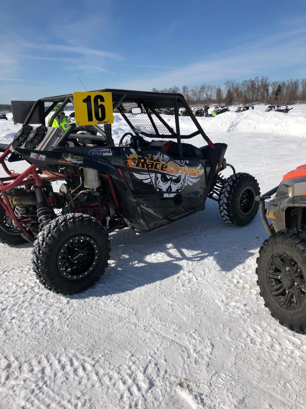 Black sxs sponsored by RaceDriven waiting to be let on the ice race track at the Twin Bridge Takedown